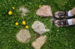 Pieds du ` s de femme sur l'herbe verte, pierres Photo libre de droits