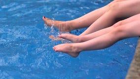 Pieds du ` s de mère et d'enfant dans la piscine banque de vidéos
