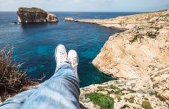 Pieds du ` s de voyageur dans des espadrilles blanches au bord de bord de la mer rocheux Images libres de droits
