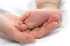 Pieds en gros plan de bébé dans la main de la mère Images stock