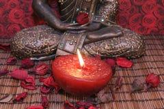 Pieds et bougie de Bouddha Photographie stock