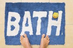 Pieds et Duckie sur le tapis de bain image libre de droits