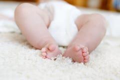 Pieds et jambes de bébé nouveau-né avec la couche-culotte Photo libre de droits