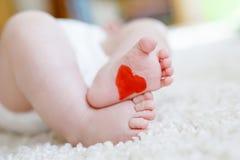 Pieds et jambes de bébé nouveau-né avec la couche-culotte Images libres de droits