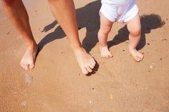 Pieds et jambes de père et de bébé Photographie stock