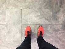 Pieds et jambes sur le plancher gris Photo stock