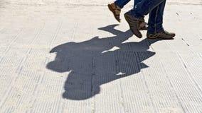 Pieds et ombre de deux marcheurs Photo stock