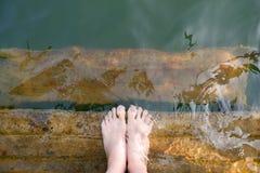 Pieds et p?dicurie de pourpre de femme dans l'eau verte, vue sup?rieure Belles jeunes jambes asiatiques de corps f?minin et nu-pi photo libre de droits