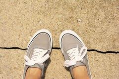 Pieds faisant un pas sur une fente de trottoir Photographie stock