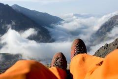 Pieds fatigués du grimpeur dans les chaussures sur des montagnes image stock