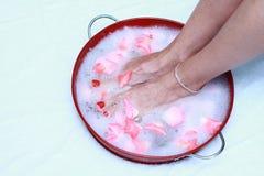 Pieds fatigués imbibant dans les bulles des pétales roses Photographie stock