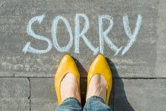 Pieds femelles avec désolé des textes écrit sur l'asphalte photo stock