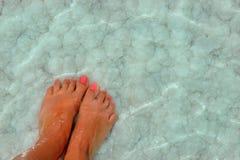 Pieds femelles avec la manucure sur la pierre, couverte de formations de sel entre les vagues dans l'eau Cristallisation de sel s photo stock