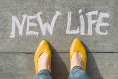 Pieds femelles avec la nouvelle vie des textes écrite sur le trottoir gris photos libres de droits