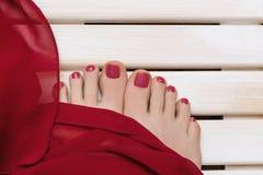 Pieds femelles avec la pédicurie rouge sur le fond en bois image libre de droits