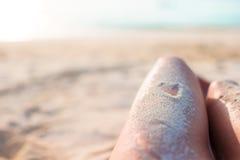 Pieds femelles avec le dessin de coeur par le sable Photo stock