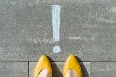 Pieds femelles avec le point d'exclamation, symbole de l'attention dessiné sur l'asphalte photos stock