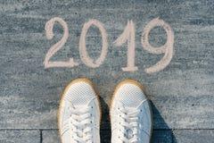 Pieds femelles avec le texte 2019 écrit sur l'asphalte image stock