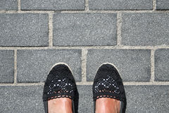 Pieds femelles bronzés sur le trottoir de granit Images stock