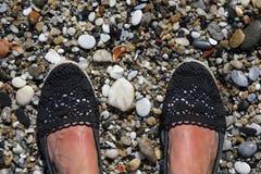 Pieds femelles bronzés sur une plage rocheuse Photo libre de droits
