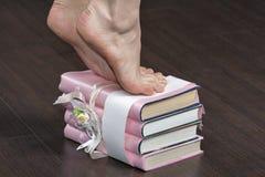 Pieds femelles caucasiens tenant la pointe du pied sur la pile du plan rapproché de livres Photos stock