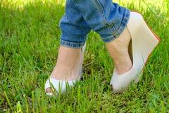 Pieds femelles dans des chaussures avec des talons de cale sur l'herbe verte Images stock