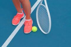 Pieds femelles dans des espadrilles avec de la balle de tennis et la raquette sur le court de tennis Images libres de droits