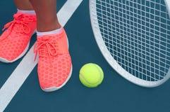 Pieds femelles dans des espadrilles avec de la balle de tennis et la raquette sur le court de tennis Photo libre de droits