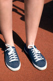 Pieds femelles dans des espadrilles bleues un jour ensoleillé Photo libre de droits