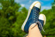Pieds femelles dans des espadrilles de jeans sur le fond d'un ciel et d'un arbre Image stock