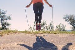 Pieds femelles dans des espadrilles sautant sur une corde à sauter Image libre de droits