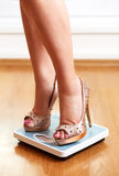 Pieds femelles dans des stylets d'or avec l'échelle de poids Photographie stock