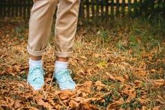 Pieds femelles dans le pantalon beige et des espadrilles d'une turquoise Photographie stock libre de droits