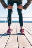 Pieds femelles dans le pantalon et des espadrilles de sports Photographie stock libre de droits