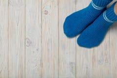 Pieds femelles dans les chaussettes bleues tricotées sur le fond en bois blanc Photographie stock libre de droits