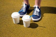 Pieds femelles dans les espadrilles bleues et des deux tasses de café un jour ensoleillé Photos stock