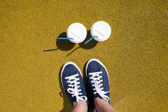 Pieds femelles dans les espadrilles bleues et des deux tasses de café un jour ensoleillé Image stock