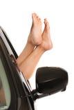 Pieds femelles de bâton hors de fenêtre de voiture photographie stock libre de droits