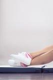 Pieds femelles de jambes dans des espadrilles sportives blanches Images libres de droits
