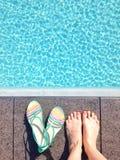 Pieds femelles du ` s par une piscine Photos libres de droits