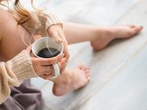 Pieds femelles et une tasse de café photographie stock libre de droits