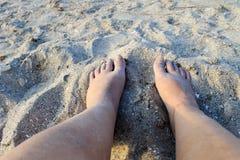 Pieds femelles sur la plage sablonneuse Photos libres de droits