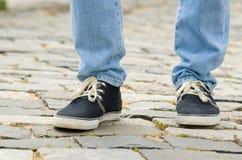 Pieds habillés dans les blues-jean et l'homme d'espadrilles Photographie stock libre de droits