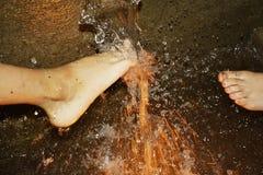 Pieds jouant dans l'eau en baisse photographie stock