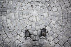 Pieds masculins dans de nouvelles chaussures brillantes noires sur des pierres Image libre de droits