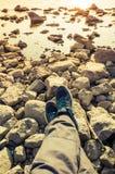 Pieds masculins dans des chaussures bleues de sport sur des roches Photographie stock libre de droits