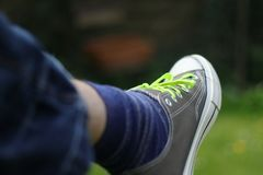 Pieds masculins dans des chaussures en caoutchouc avec la dentelle jaune images stock