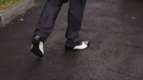 Pieds masculins dans des chaussures en cuir brillantes noires faisant un pas sur Asphalt Pavement banque de vidéos