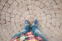 Pieds masculins dans les blues-jean et des espadrilles Images libres de droits