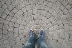Pieds masculins dans les jeans et des espadrilles bleu-foncé Photos stock